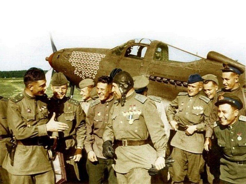 Боевые товарищи поздравляют Покрышкина (в шлемофоне) с присвоением ему в третий раз звания Герой Советского Союза. Лето 1944 года.  На заднем плане истребитель американского производства P-39 «Аэрокобра» (Bell P-39 Airacobra) Речкалова.