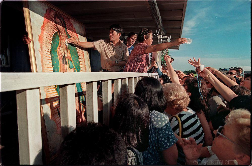 """Dade City, Florida: Peregrinos se juntaram ao redor da varanda com a família de Vimer Nagun que distribuia 'bolas de algodão com que limpava de sobre a pintura da Virgem Maria que vertia lágrimas de óleo"""". Milhares de peregrinos visitaram a casa durante os primeiros dias de aparições de Nagun. (Photo by Robert Falcetti)."""
