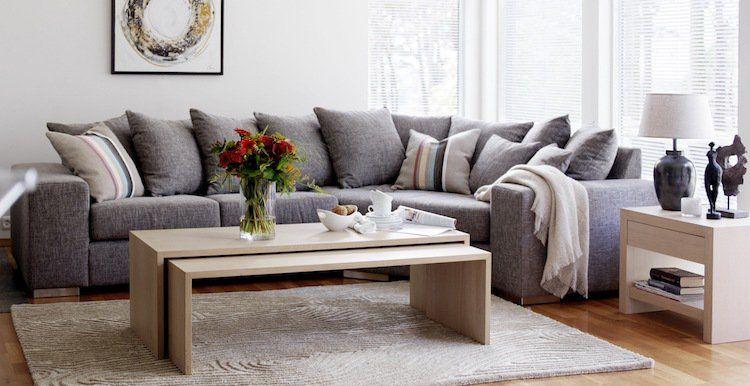Canapé dangle gris décoré de plusieurs coussins gris table gigogne en bois