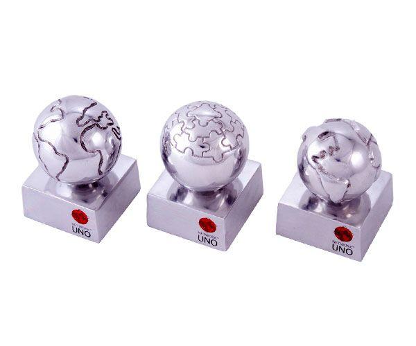 Peça: tridimensional com relevos, 6cm de diâmetro.  Materiais disponíveis: alumínio (prata) ou bronze (dourado ou patinado).  Base: madeira natural ipê, madeira revestida de fórmica preta ou metal 6,5x6,5x3cm.  Placa cortesia: aço inox (prata) ou latão (dourada), 5x2cm ou impressão em silk.