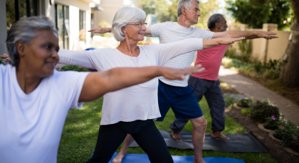 group of older yoga students practicing warrior ii pose