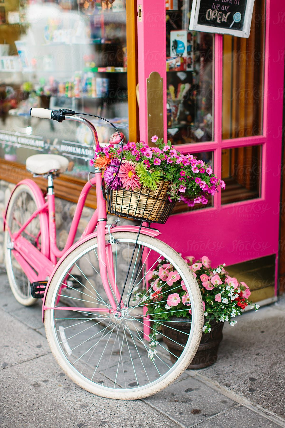 A pink cruiser bike with flowers infront of a candy store by Kristen Curette Hines for Stocksy United