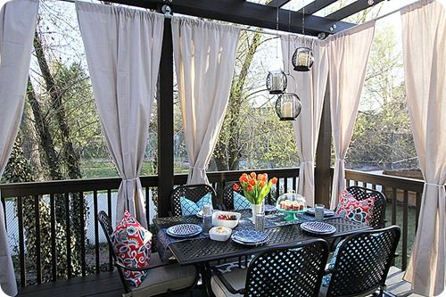 Consider adding drapes and fun pillows to decorate your patio furniture.