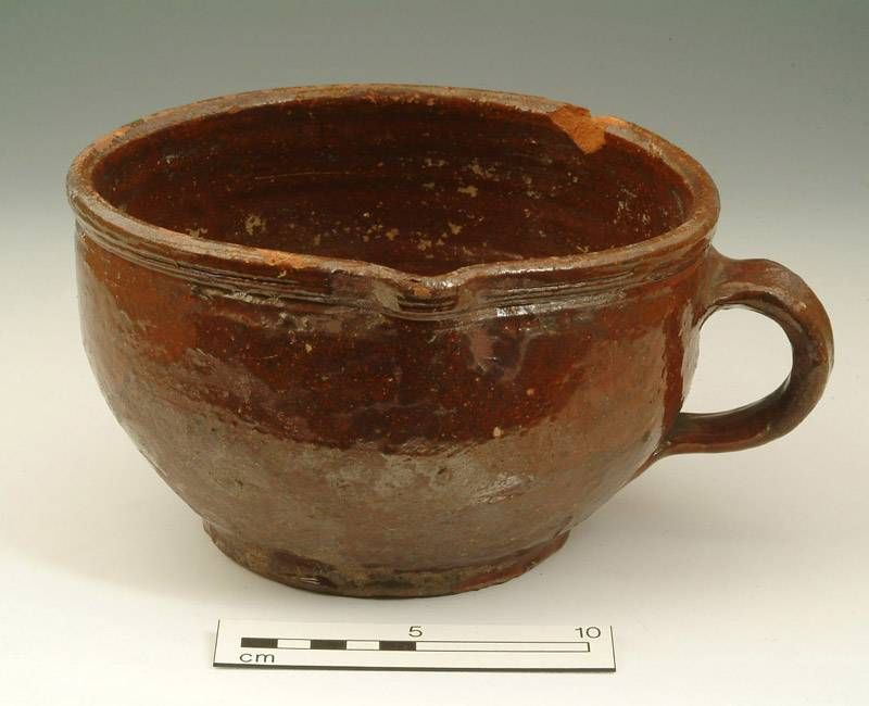 Accession number: A26125 Collection place: Harlow, Essex Production date: 1580-1700 Material: ceramic; earthenware Measurements: H 125 mm Museum Section: Post-Medieval Summary: Post-medieval fine redware handled bowl with pinched pouring lip and glazed inside and out.