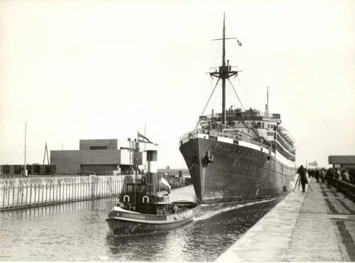 The first ship passing through the newly opened Northern sea lock at IJmuiden in 1930.