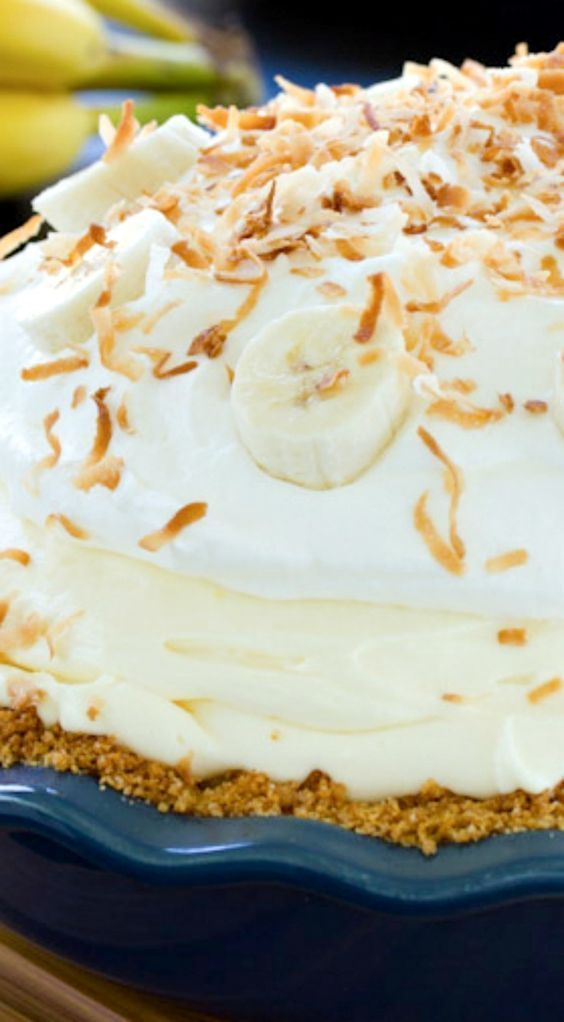 Banana Cream Pie Recipe ~ is piled high with fresh ripe bananas and creamy vanilla filling, then topped with pillowy whipped cream and toasted coconut.