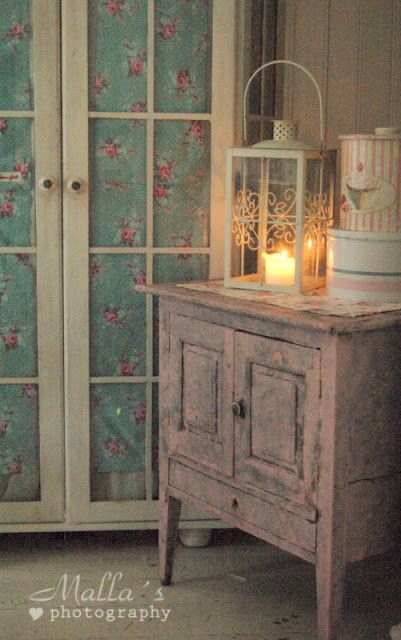painted cupboard with  fabric behind doors
