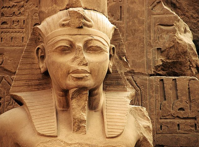 One of the many weathered statues adorning the Temple of Ramses III, part of the Karnak temple complex.