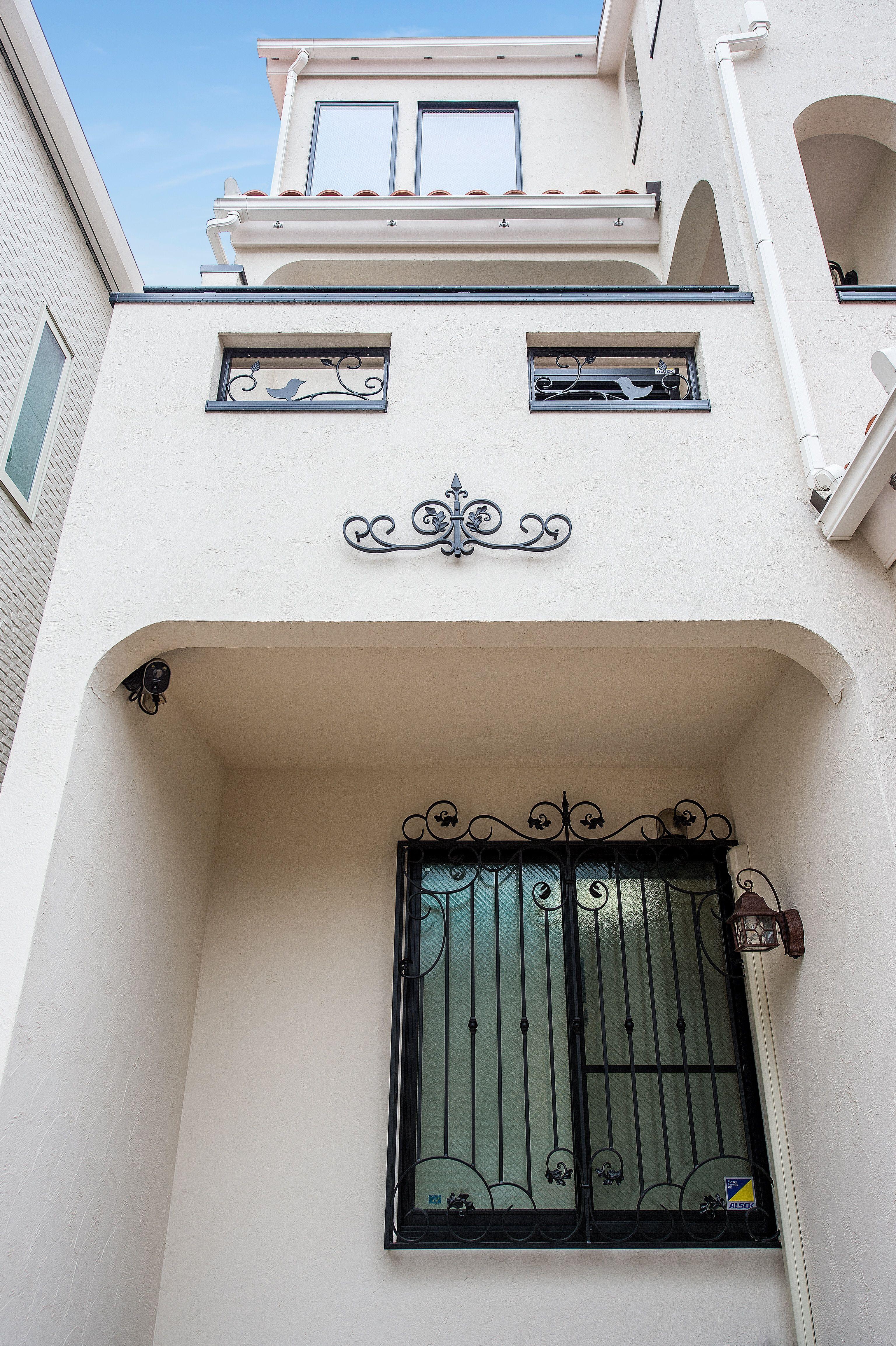 お施主様こだわりのオーダー面格子と妻飾りは曲線が美しい。2階バルコニー開口にある鳥をモチーフにした飾り格子はスペースラボオリジナル