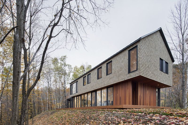This cedar shingled house is at home surrounded by the forest in ...