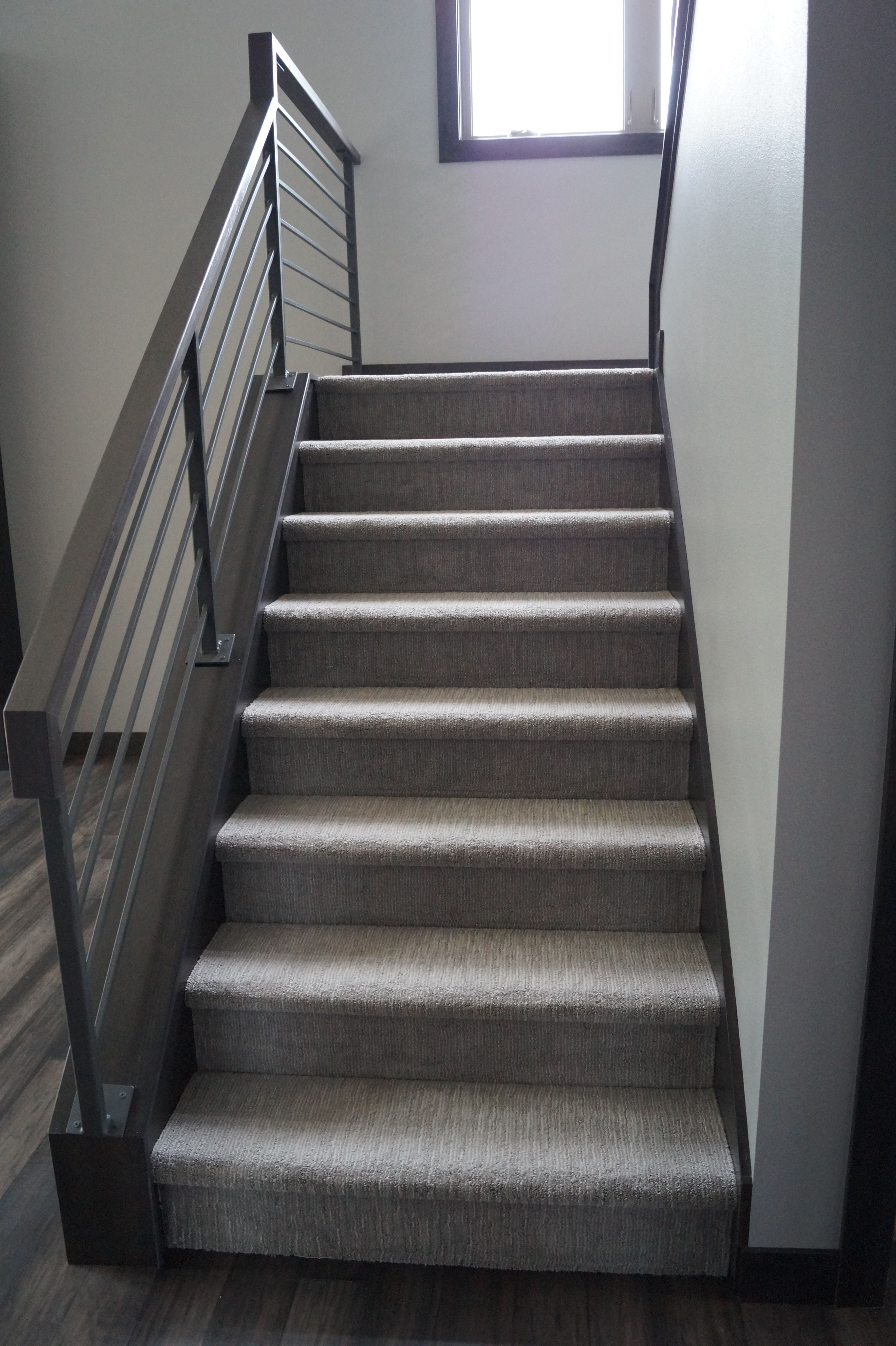 patterned carpeted stairs with custom metal railing