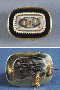 "A lock of hair from the head of Napoleon Bonaparte, the lock in a figure of eight is set amongst gold and silver formal foliage, at the centre an 'N' beneath glass, it is framed in a brooch with a line of pearls and black enamel, the back is engraved ""Napoleon Bonaparte lock of his hair, given to Mrs Riley, Major Poppleton 27 July 1821"". Captain William Thomas Poppleton of the 53rd Regiment acted as the Emperor's orderly, they were almost in daily contact."