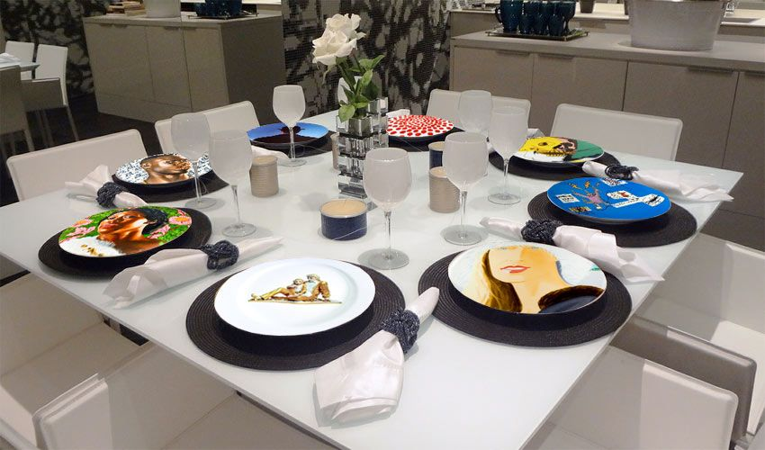 table setting with artist plates featuring fine art, including work by Alex Katz, Andy Warhol, Kehinde Wiley, Jean-Michel Basquiat, and more.