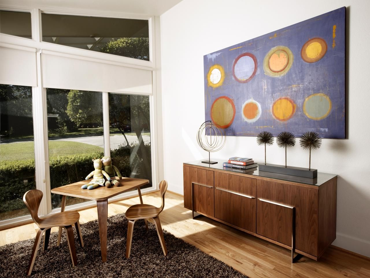 Colorful artwork and a wood console table for toy storage make this