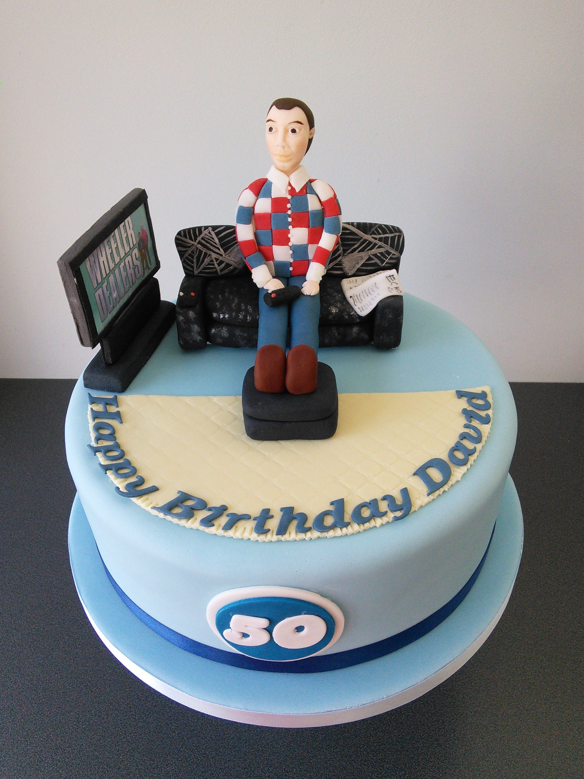 Man on couch watching wheeler dealers 50th birthday cake