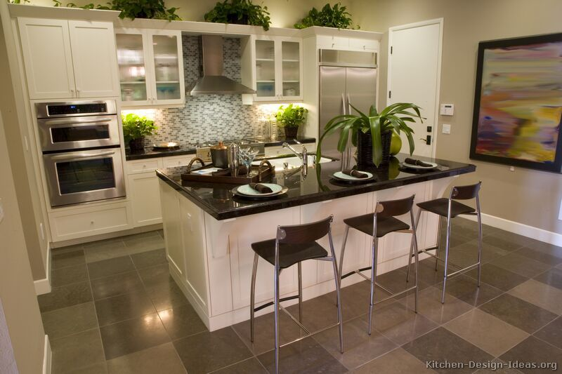 A Transitional Kitchen Design With White Cabinets, A Blue Glass Tile  Backsplash, Gray Floors