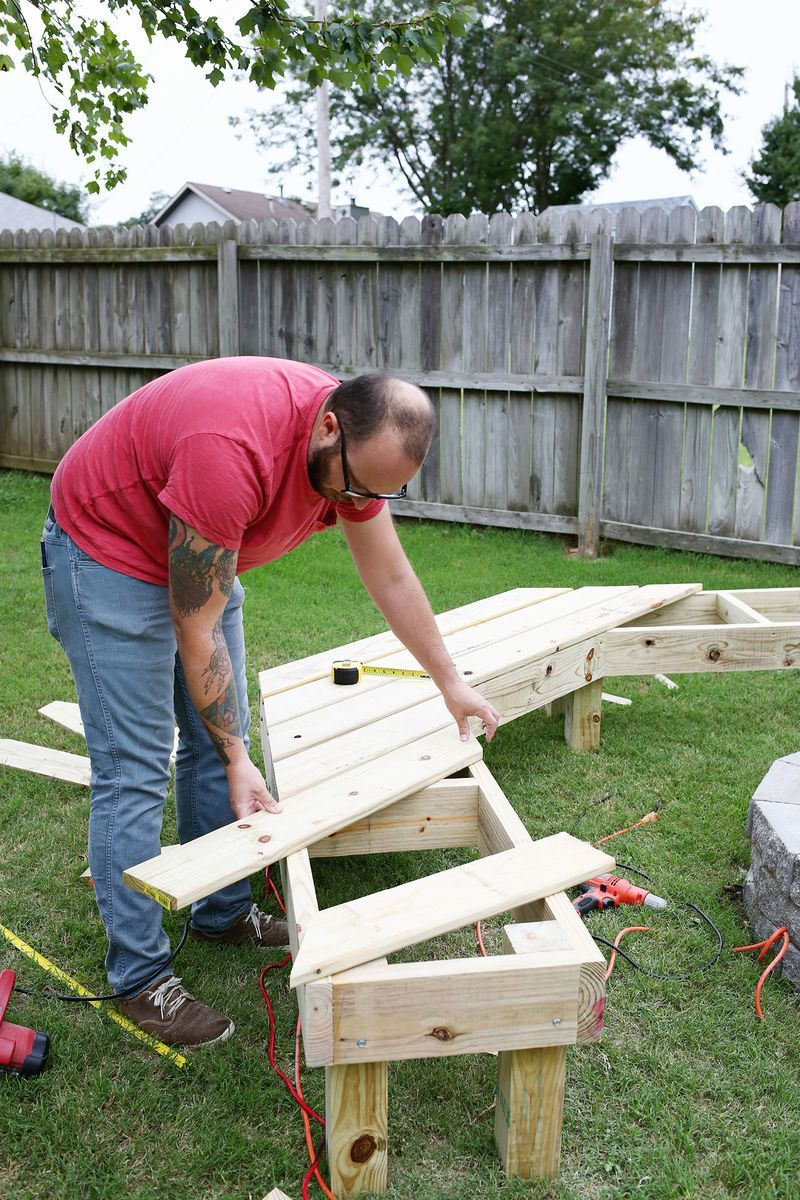 man lays a wooden frame in his backyard then flips it over to