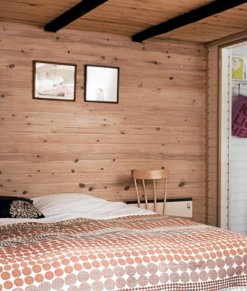 På soverommet har veggpanelet sluppet unna malingskosten, og både tak og vegger er i en lun trefarge. Bjelkene i taket har derimot blitt malt svart. Sengeteppet tar opp fargen i panelet.