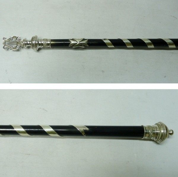 A handsome antique silver and ebony baton from Hungary. Extra long size and probably originally used in a military band. The centre has a spiral band of silver decoration and at each end the baton has a decorative finial, one formed as a musical instrument. Length 49 cms. Marked on the centre strip and top finial with Hungarian marks. Circa 1930.