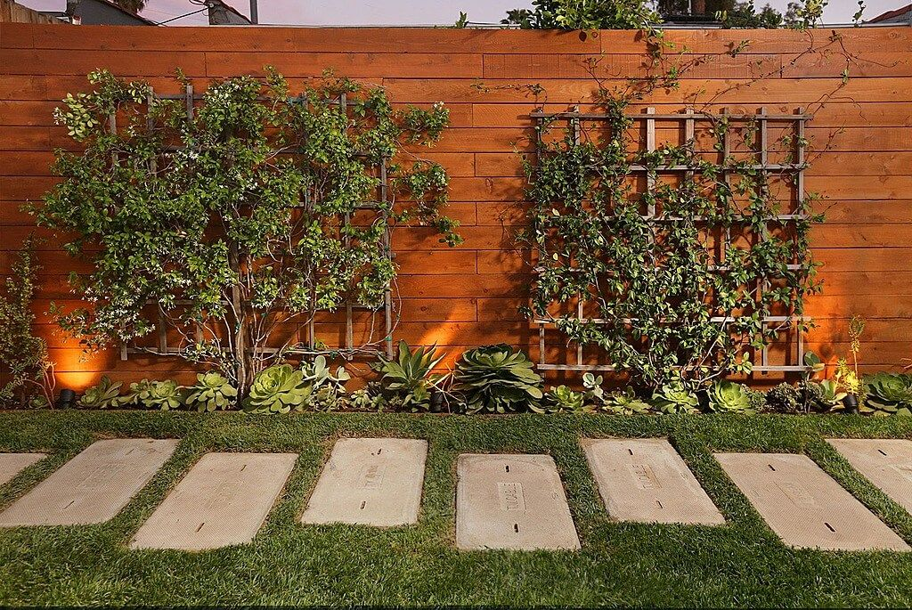 this warm wood privacy fence design features attached lattice mounted greenery - Fence Design Ideas
