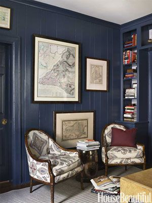 Painting the paneled walls and cabinets of the library deep blue gave a sliver of a room impact. Design: Lindsey Coral Harper.