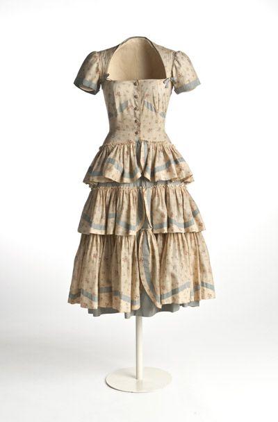 Vestido   1949  Vestido realizado en batista (tejido muy fino en tafetán de algodón) o con decoración estampada de pequeños ramilletes florales y cintas grisáceas en los remates de las mangas y los tres volantes de la falda.  MT104953