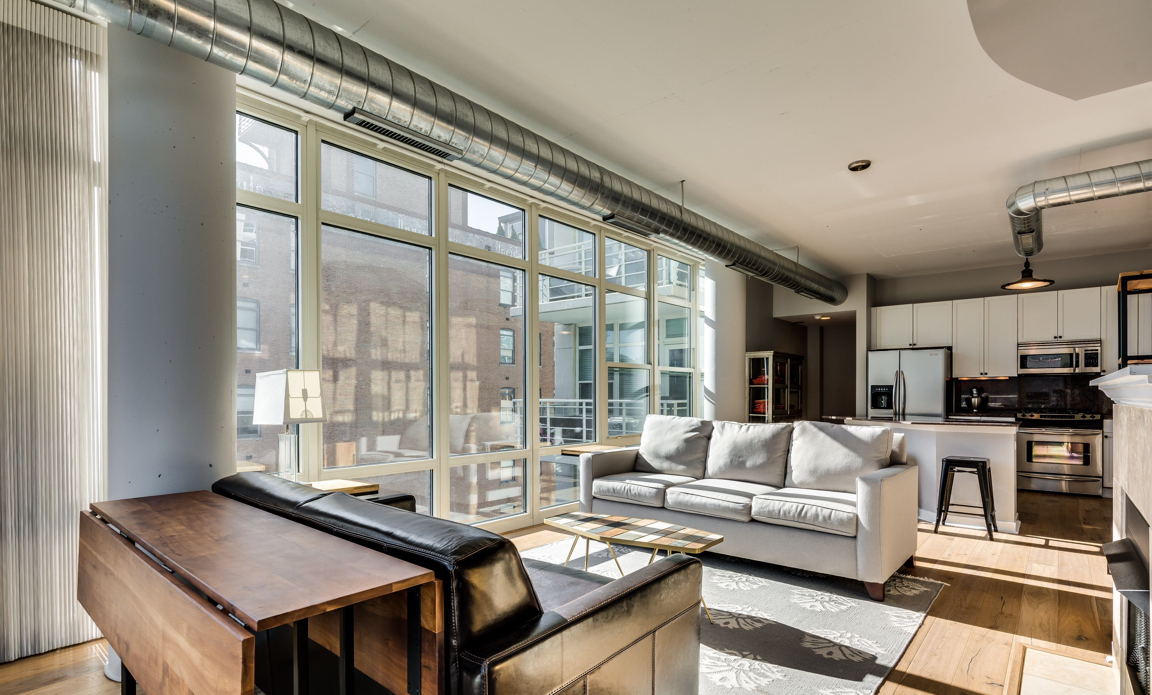 Modern city apartment with exposed ductwork, hardwood floors ...