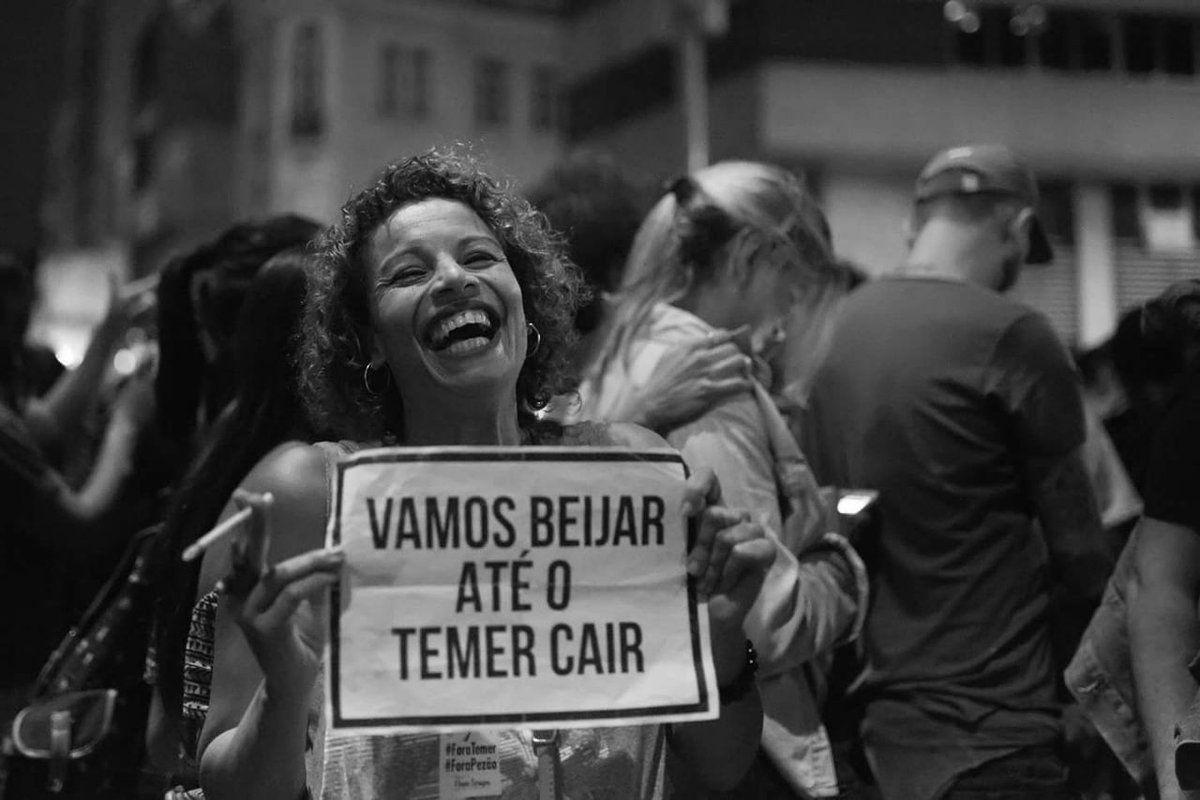 """Moça sorri efusivamente em manifestação contra o atual governo segurando cartaz onde se lê """"Vamos beijar até o Temer cair""""."""