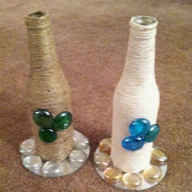 These are empty beer bottles wrapped with yarn, an old CD, and decorative stones.  Very simple to do.