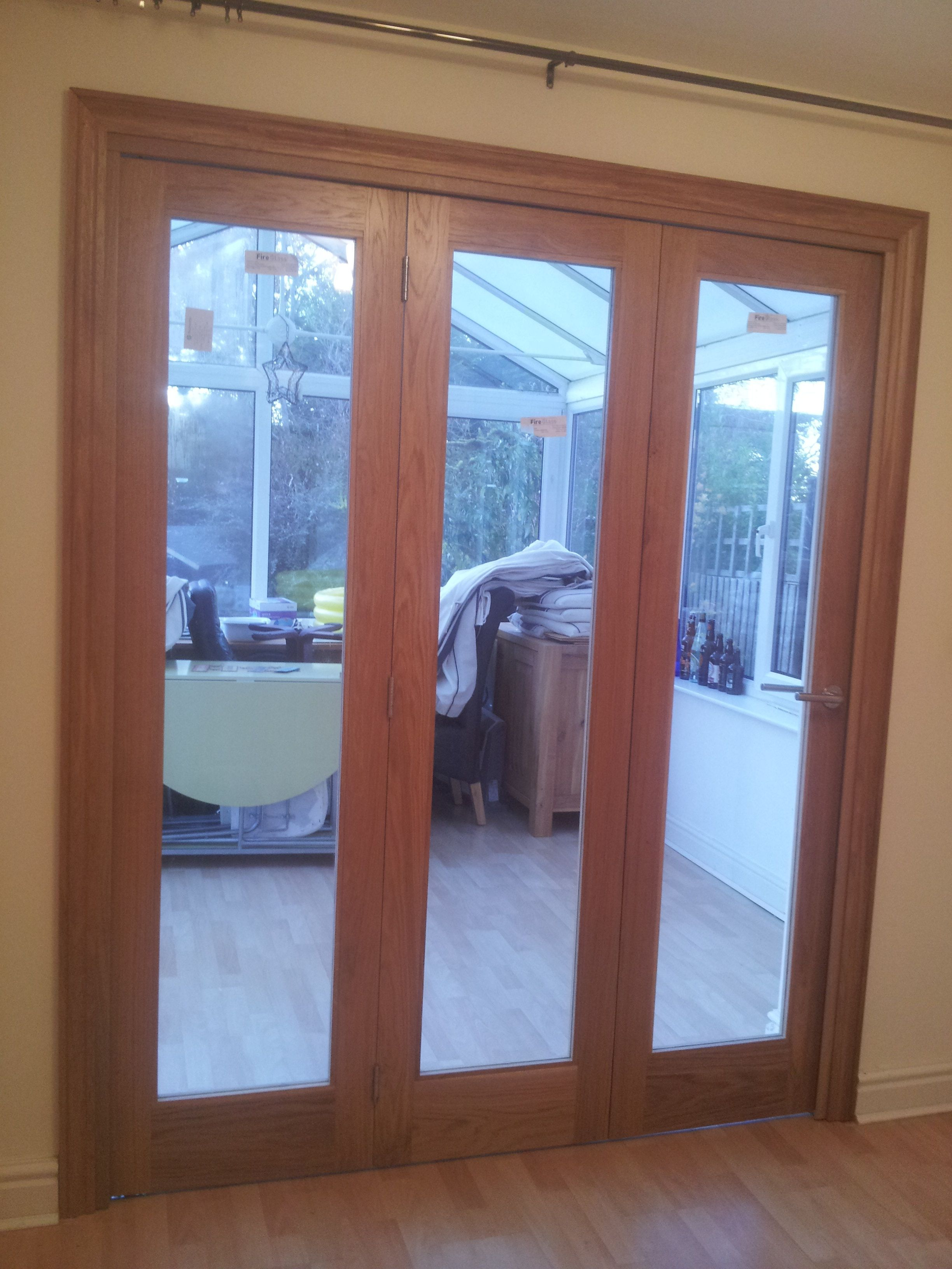 Tri fold sliding room divider in white oak with clear safety glass