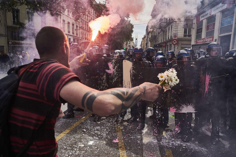 Um homem segura um buquê de flores e um sinalizador enquanto enfrenta a polícia durante uma manifestação contra a reforma trabalhista planejada pelo governo, em 26 de maio de 2016, em Lyon, na França. (Jean-Philippe Ksiazek / AFP / Getty)
