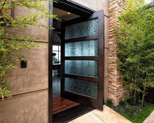 Cette image montre une porte d\u0027entrée design avec une porte pivot et