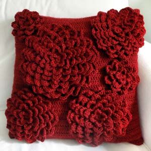 Crochet Spot Flower Pillow Cover - each flower is crocheted separately and sewn onto the cover. Love the retro style - reminds me of the pillows my great-grandma had!