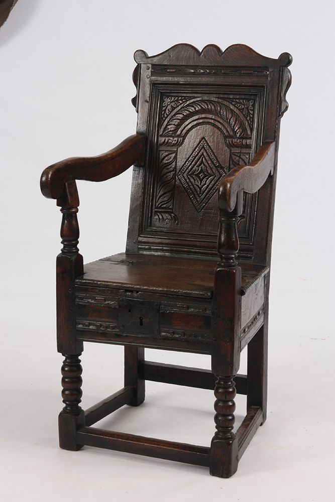 A 17TH CENTURY BOX SEAT CHILDS OAK WAINSCOT CHAIR Having A Shaped Carved  Back And Hinged