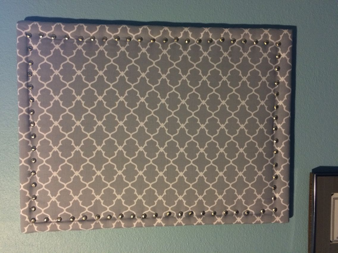 Used cork board with some batting and fabric, then I outlined it with silver rounded tacks. Easy and inexpensive!