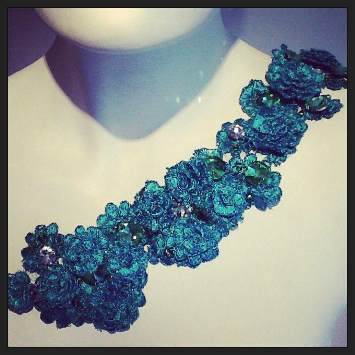 Detalle de tirante, flores tridimensional en color verde Esmeralda, piedras hectogonal plata.