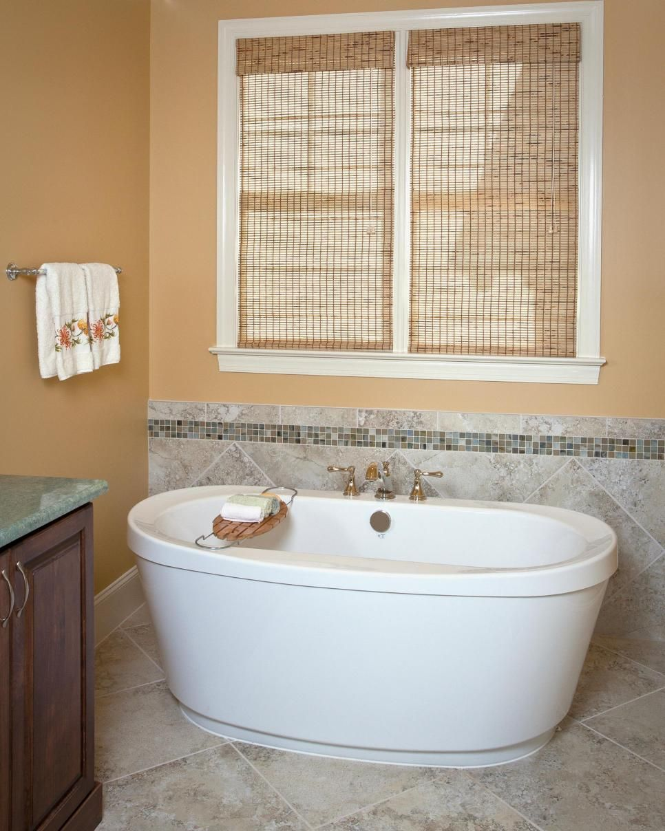 This neutral bathroom features bamboo Roman shades, a large soaking ...