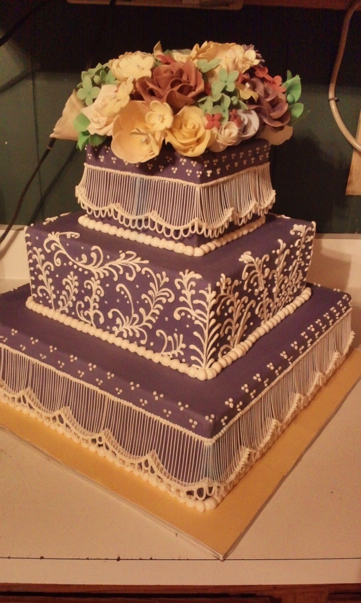 Square wedding cakes covered in a purple fondant with royal icing