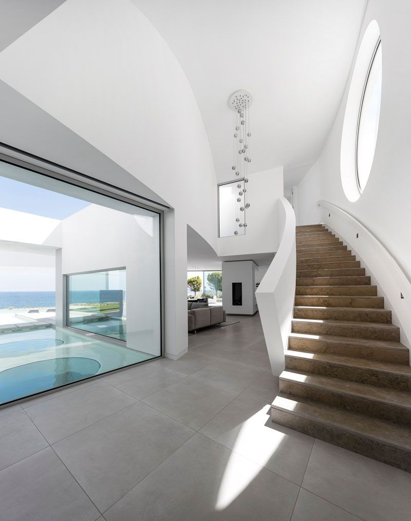 Inside this modern house with a white interior is a curved staircase with a large circular window that leads you to the upper level of the home