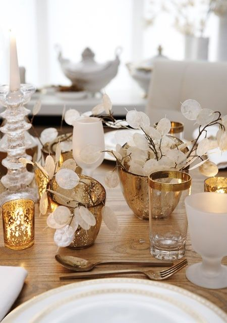 Silver dollars in speckled gold-leaf vessels are a simply sophisticated way to set a holiday table. White china and milky, translucent wine glasses keep the table looking natural and glamorous. Chunky glass candlesticks look like delicate ice carvings.