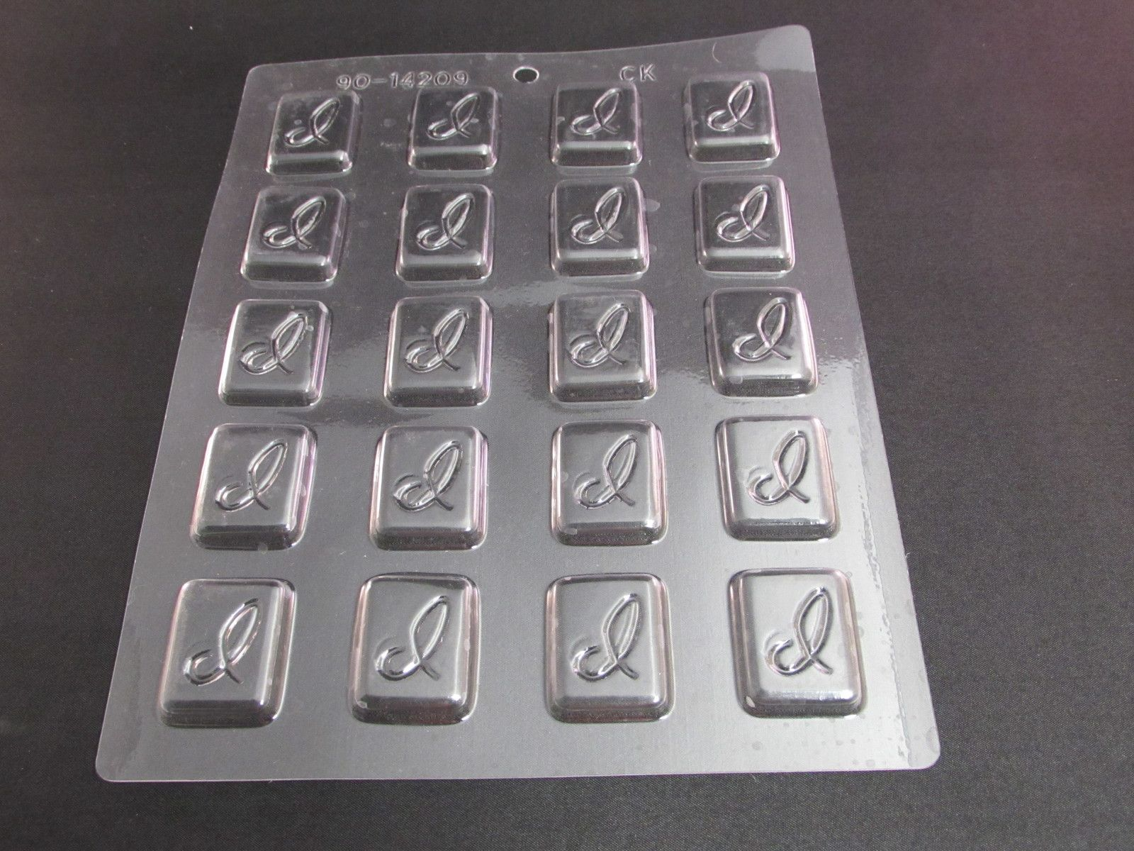 Initial I Candy Mold. This is a CK Products mold for making hard candies. The design is little rectangles with the Initial I on it. The model number is 90-14209. There are 20 spots on the mold. It has been used and does show signs of use along with being a little warped.