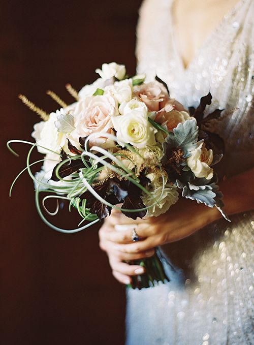 A tight bouquet of air plants, quicksand roses, white spray garden roses, white Ranunculus, Astilbe, Dusty miller and plum foliage. PHOTO: Braedon Flynn Photography.