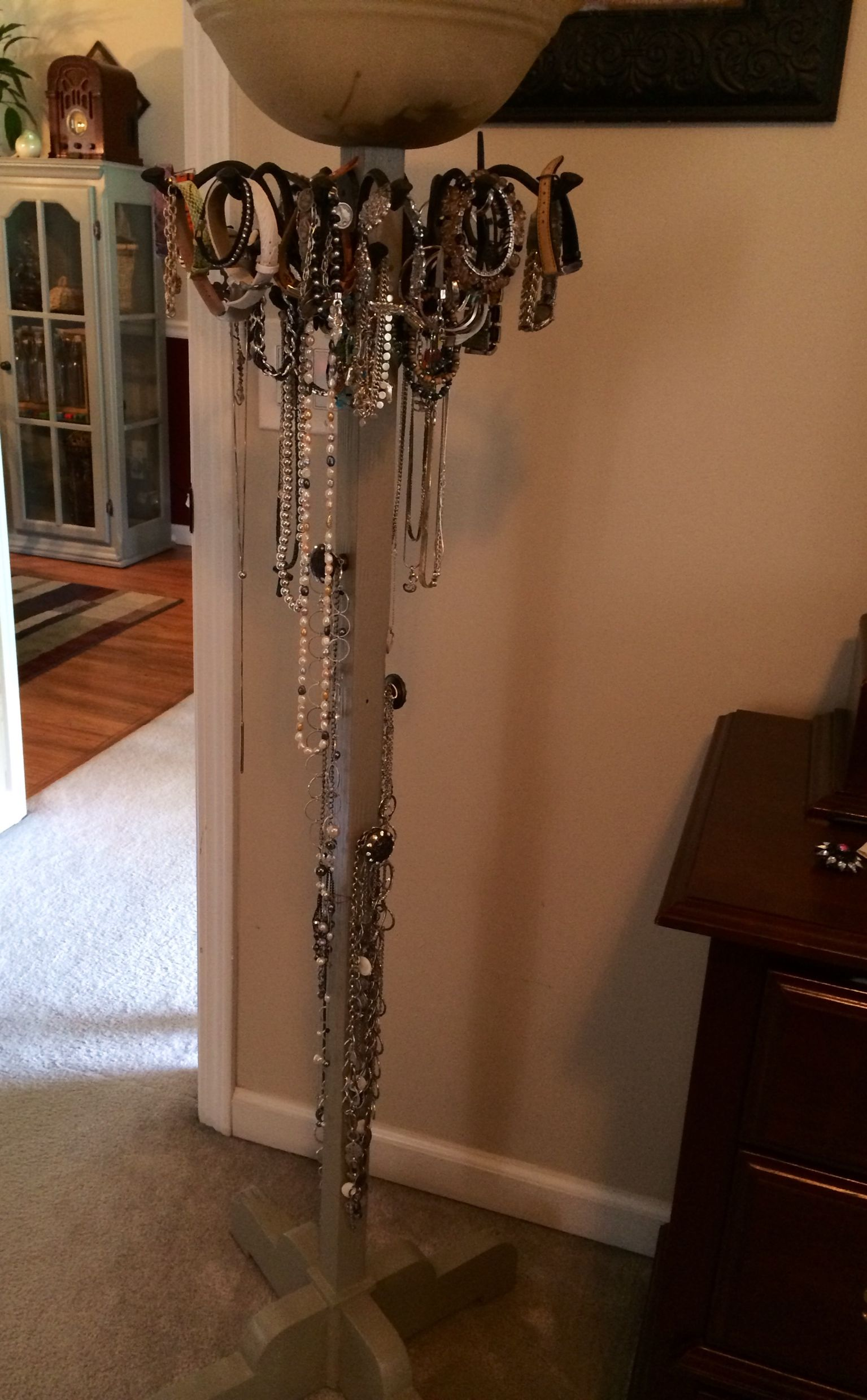 old coat rack with knobs and light fixture to make a jewelry holder