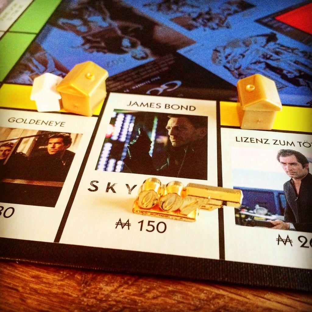 """Monopoly James Bond 007 - Sie ziehen durch die ersten 23 Bond-Abenteuer – von """"Dr. No"""" bis """"Skyfall"""" und tauchen ein in eine Welt voller Schurken, schneller Autos, Bondgirls und technischer Spielereien. Nach dem bekannten Monopoly-Prinzip bauen Sie Verstecke und Hauptquartiere, erwerben klassische Bond-Autos und kommen hin und wieder mal ins Gefängnis."""