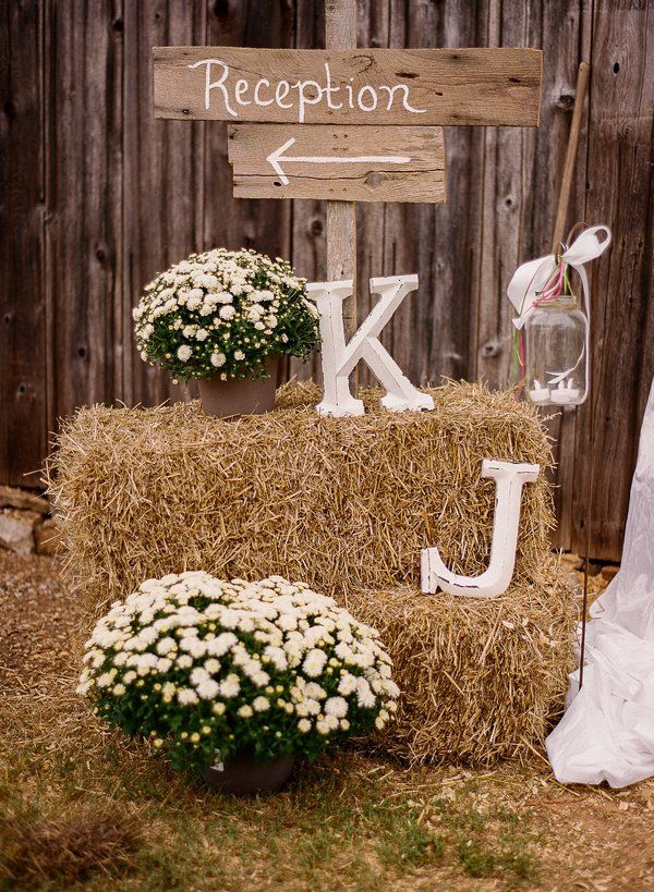 Country Wedding Sign, note use of mum planters, hay bales, and prepared letters, candles near hay make me uncomfortable.
