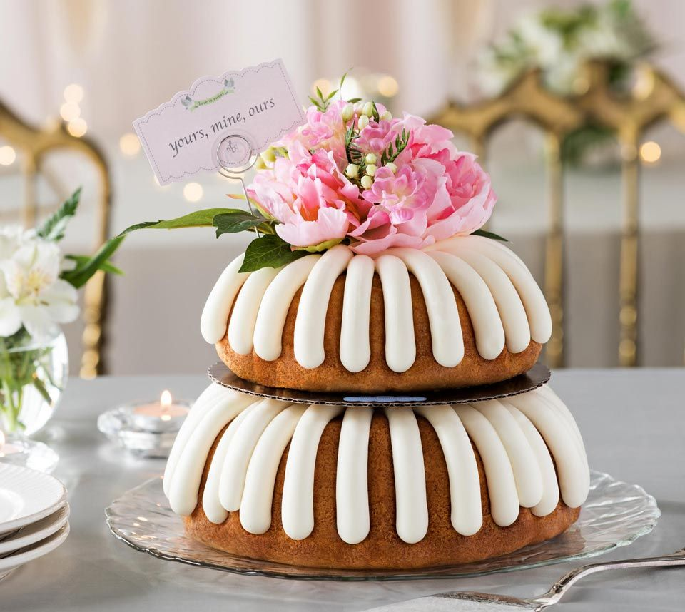 A twotiered bundt cake with plates and a cake server in