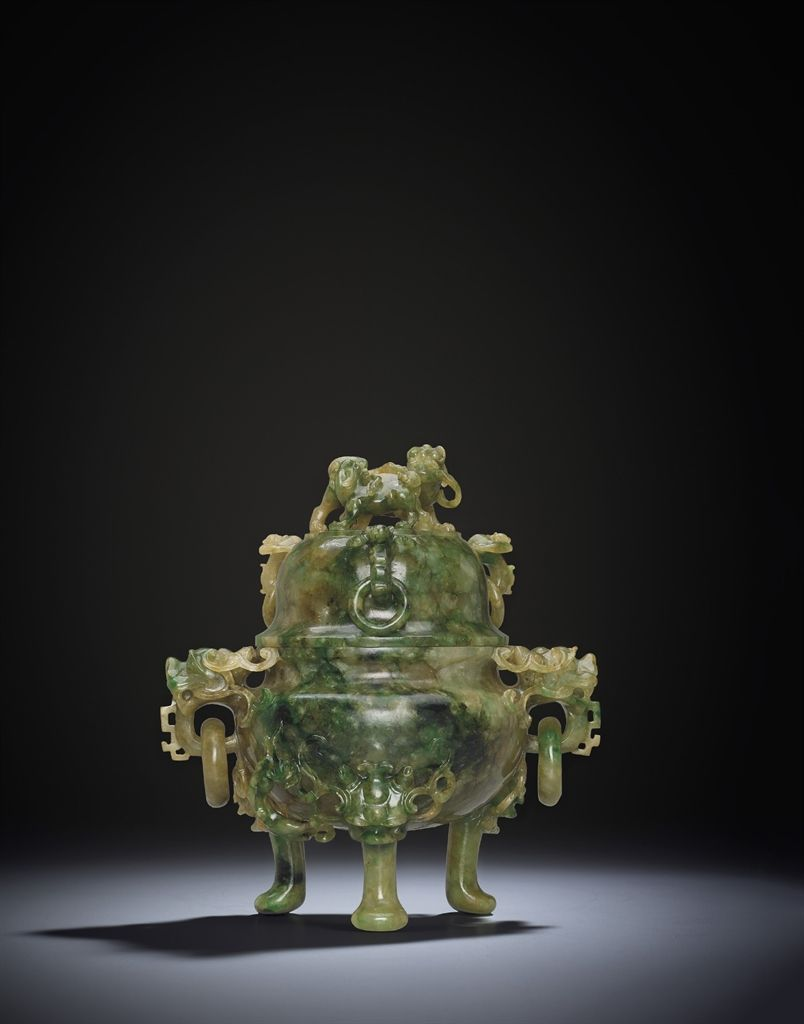 A JADEITE TRIPOD CENSER AND COVER -  The compressed globular censer is carved and pierced with prominent dragon-head handles each suspending loose circular rings. It is all raised on three short cabriole legs emerging from lion-masks, the domed cover surmounted by a pair of Buddhist lions and further embellished with three bat form handles with loose rings.