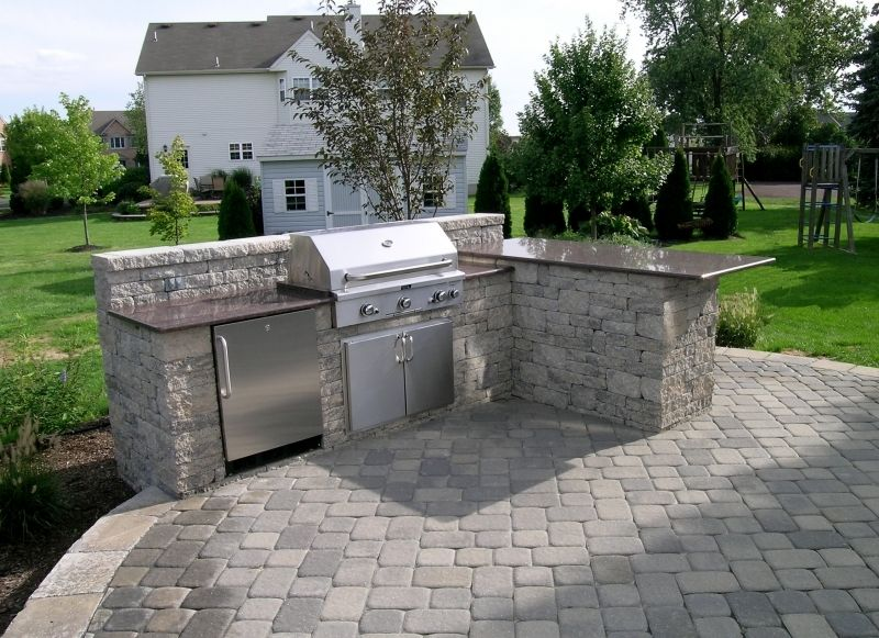 An Outdoor Kitchen Area, Custom Patio Landscaping And Landascape Lighting  Featuring Lighting Under The Countertops