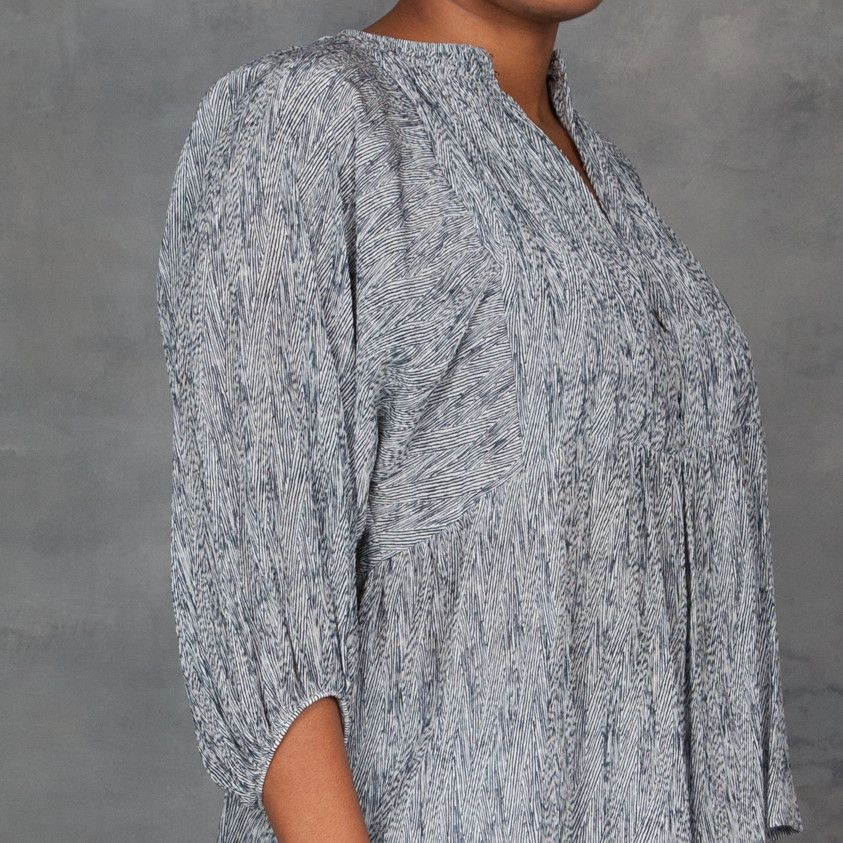 A voluminous Apiece Apart tunic top, detailed with a smocked neckline. Gathered elastic cuffs cinch the cropped dolman sleeves, and hook and eye closures secure the quarter placket