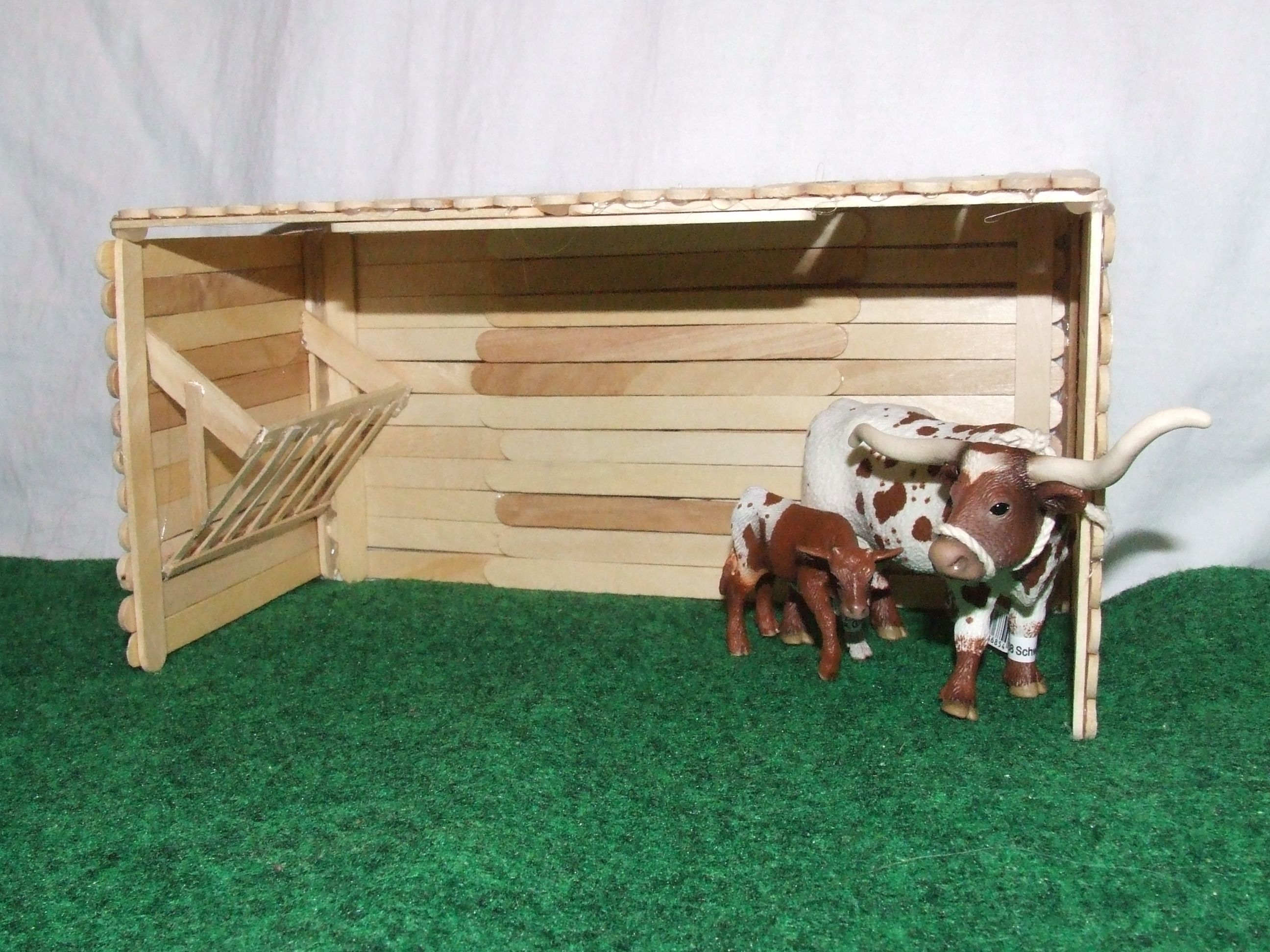Photo of DIY Run-in shed with hay manger. Made with popsicle sticks, coffee stirs, and a …